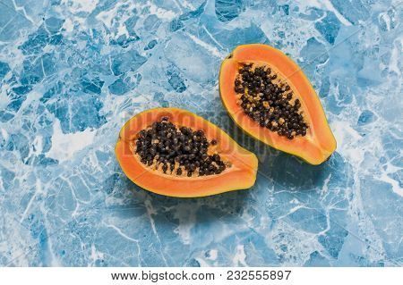Two Halves Of Papaya On A Bright Blue Background. The View From The Top