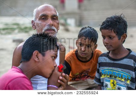 VARANASI, INDIA - MAR 16, 2018: Unidentified indian street children and a grown man on the banks of Ganga river. According to legends, the city was founded by God Shiva about 5000 years ago.
