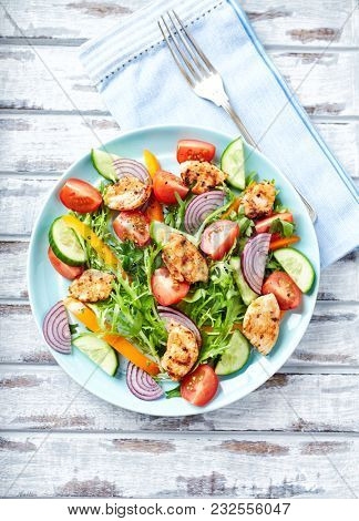 Chicken Salad with Colorful Vegetables: Cherry Tomatoes, Cucumber and Red Onion. Top view. White Background.