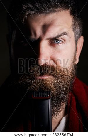 Handsome Young Bearded Man Trimming His Beard With A Trimmer. Male Is Trimming His Facial Hair. Port