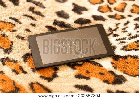 Tablet With A Broken Screen On The Background Of Tiger Skin .
