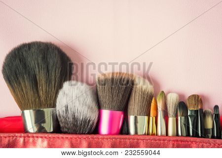 Many Fashion Brush For Makeup Or Cosmetic In Red Bag On Blurred Pink Background. Beauty Visage And D