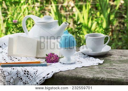 Breakfast With Cup Of Coffee. Egg On White A Lace Tablecloth With Green Grass Background.