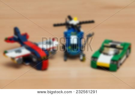 Blur Image Of Aeroplane, Helicopter And Car Toys On Wooden Floor.