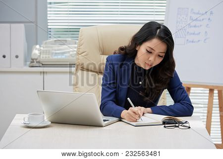 Concentrated Asian Businesswoman With Long Curly Hair Sitting At Office Desk And Taking Notes While