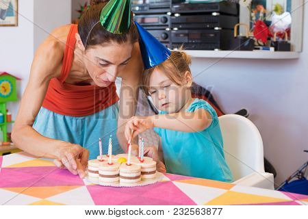 Child And Mother Putting Candles On Party Cake