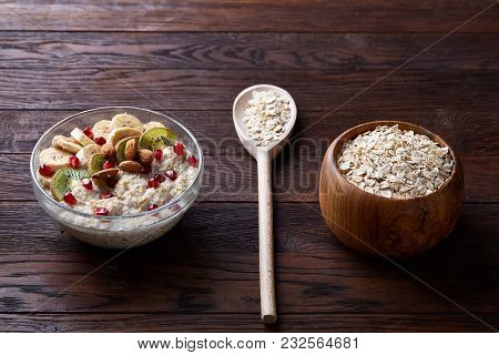 Composition With Transparent Bowl Of Oatmeal Porrige With Banana, Kiwi, Almond, Pomergranate, Dry Oa