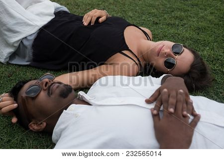 Close Up Portrait Of Just Married Couple Lying On Grass Together In Love. Concept Of International M