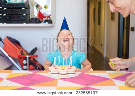 Little Child With Birthday Cake Horselaughing Next To Woman