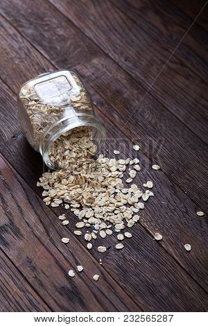 Overturned Glass Jar With Raw Oatmeal On Vintage Wooden Background, Close-up, Top View, Selective Fo