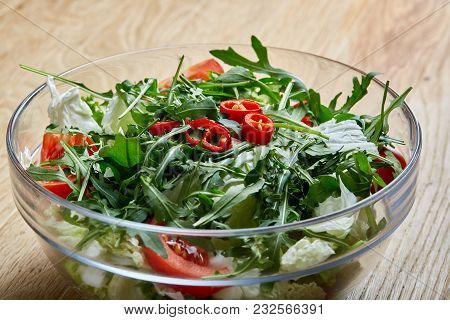 Spring Dietary Mixed Salad With Ruccola, Lettuce, Tomatoes And Hot Pepper In Transparent Glass Sulta