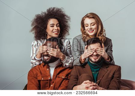 Happy Multicultural Retro Styled Girls Covering Eyes To Multiethnic Men Isolated On Grey