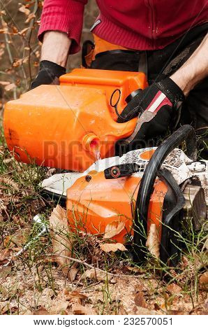Close-up Of Forestry Worker Filling Up Chainsaw With Gasoline Fuel