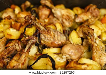 Closeup Of Grilled Chicken Drumsticks With Potato Chips