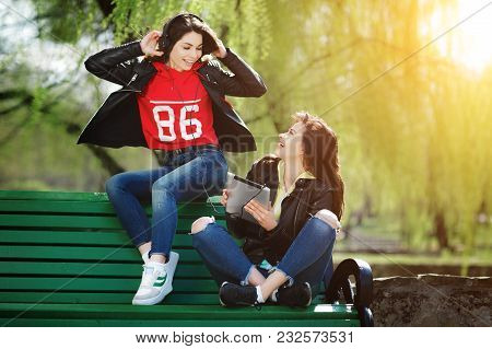 Two Pretty And Happy Young Woman Using The Tablet In The Park. Best Friends Listening Music