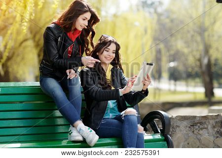 Two Pretty And Happy Young Woman Using The Tablet In The Park. Best Friends