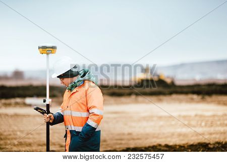 Surveyor Engineer Working With Technology For Coordinating Heavy Duty Machinery