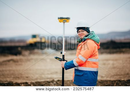 Surveyor Engineer Working On Highway Construction Site, Working With Theodolite And Gps System