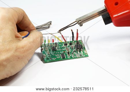 Soldering Operation. Transformer Soldering Iron, Hand, Solder. Soldering Of Wires On A Printed Circu