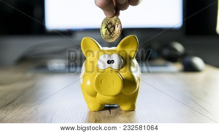 Hand Putting Golden Bitcoin In To Piggy Bank Money Box With A Computer On Background. Cryptocurrency
