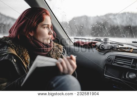 Girl Reading Book Inside The Car. Rain Drops On The Glass