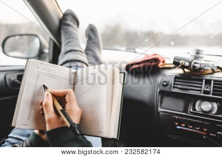 Closeup Shot Of Notebook And Pen In Hands. Inside The Car. Ready To Write