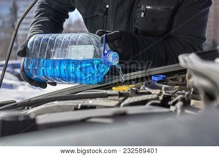 Man Pouring An Antifreeze Liquid In A Windshield Washer Tank Of A Car Standing On The Roadside