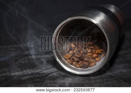 Roasted Coffee Beans Are Poured From A Cup