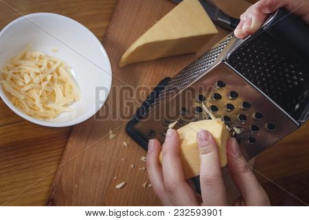 The Girl Is Rubbing Dutch Cheese On A Grater