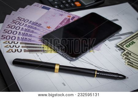Black Ballpoint Pen With A Bunch Of Euros, Dollars  And A Mobile Phone
