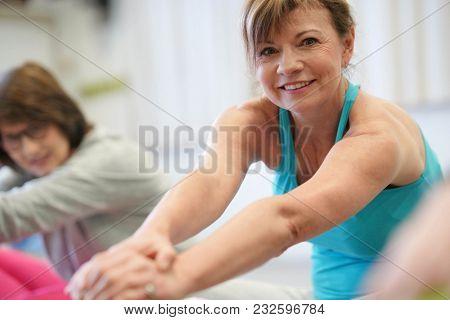 Portrait of senior woman in fitness class exercising on floor