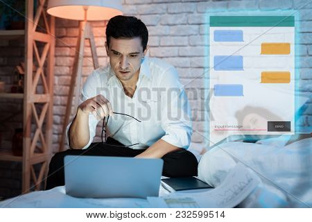 Adult Man Communicates In Chat At Night. Confident Businessman Is Chatting In Messenger. Communicati