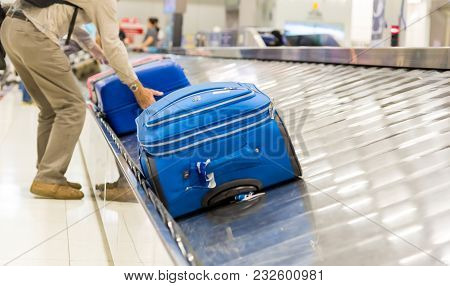 Blurry Picture Of Suitcase On Luggage Conveyor Belt At Baggage Claim At Airport. Lines Of People Wai