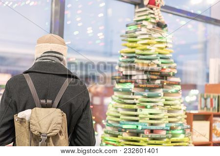 Man In A Gray Coat In A Bookshop. The Concept Of Self-education
