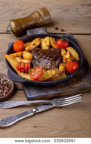 Beef With Potatos And Tomatos On Wooden Background