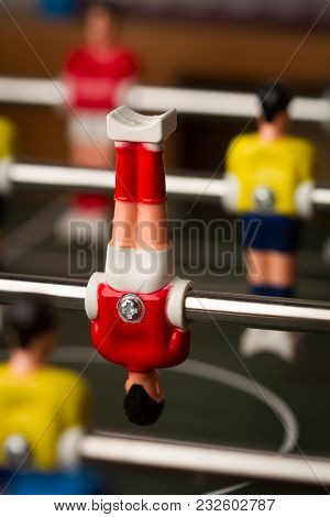 Vertical Closeup With Selective Focus Of Red Shirt Player Upside Down Figurine On Foosball Table Soc
