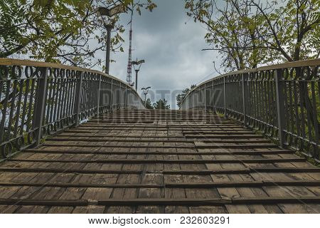 Wooden Bridge With Lanterns In Park On Dark Cloudy Sky Background. Close-up. Twilight In The Park