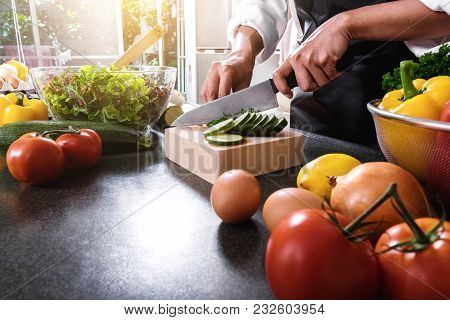 Close Up Of Woman Hand Cutting Salad On Chopping Wood Board With Sharp Knife And Cooking Vegetables