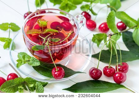 Fresh Fruit Cherry Drink In Transparent Glass Cup Surrounded By Cherries On The White Wooden Backgro