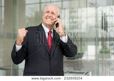 Closeup Portrait Of Cheerful Senior Business Man Celebrating Success And Calling On Smartphone At Of