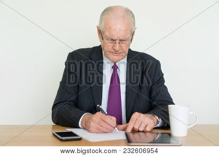 Closeup Portrait Of Focused Senior Business Man Writing And Using Tablet Computer At Office Desk. Fi