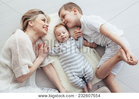 Young mom with her 5 years old son and 2 month old baby are relaxing and playing on the floor, top view from above