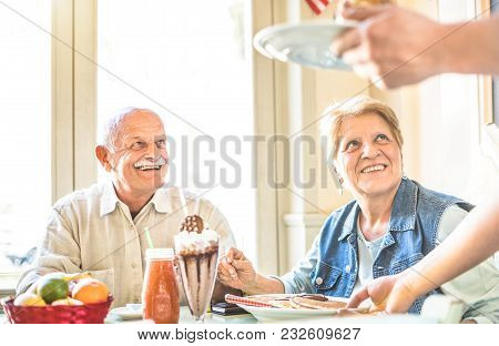 Waiter Serving Senior Retired Couple Eating Cakes At Fashion Bio Restaurant - Pension And Active Eld