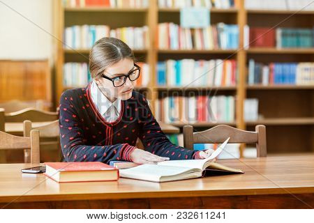 Concentrated Student Studying In Library, Young Good-looking Woman Reading Books Attentively, Wearin