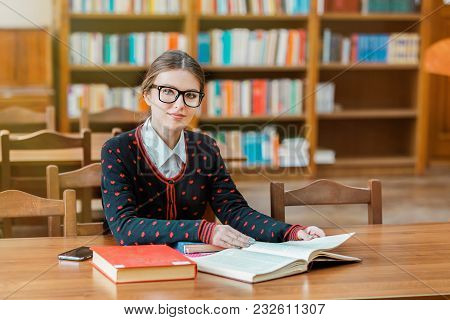 Portrait Of Concentrated Student Studying In Library, Young Good-looking Woman Reading Books Attenti