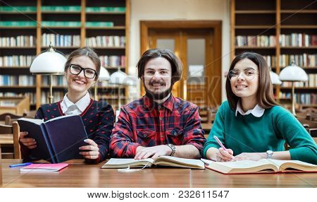 Engaged Students Checking Information In Different Booksources, Indoor Shot In College Library