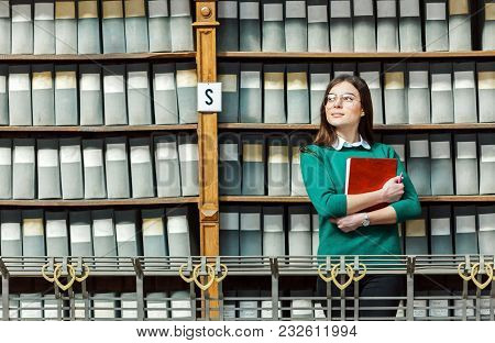 Slender Brunette Wearing Stylish Glasses And Green Sweater Holds Red Book Near Library Bookshelves W