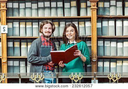 Slender Brunette Wearing Stylish Glasses And Green Sweater, Bearded Man Holds Books Near Library Boo