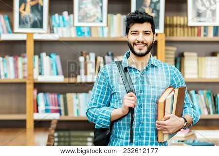 Portrait Of Smiling Awesome Man Student Holds Books And Bag In The Library