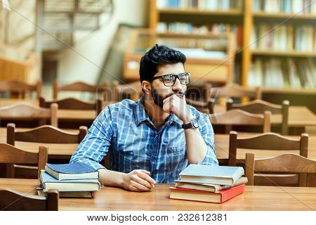 Successful Bearded Student Wears Glassses Thinking At The Table With Books In The Library Reading Ha